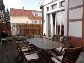 Dachterasse mit Gartenmöbeln & Grill.